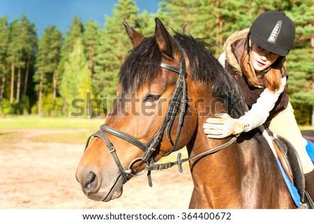 Girl equestrian riding horseback and stroking horse neck. Vibrant summertime horizontal outdoors image. - stock photo