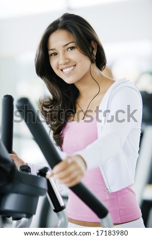 Girl exercising at the gym on stepper machine - looking happy - stock photo