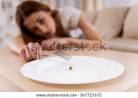 Girl exhausted from malnutrition lies on the sofa. Plate is empty side and closeup on the photo - stock photo