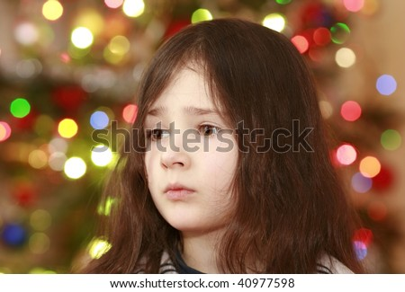 girl face on the christmas tree with colorful lights background, expecting of gifts - stock photo