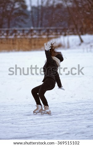 Girl falling down while ice skating in winter rink. Skating involves any sports or recreational activity which consists of traveling on surfaces or on ice using skates. Selective focus. - stock photo