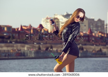Girl fashion model hipster drinking coffee on the background of the city on the waterfront
