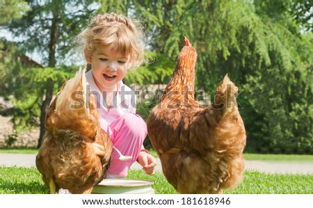 Girl feeding chickens in farm