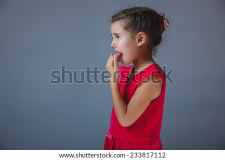 girl fingers in his mouth in a red dress on a gray background - stock photo