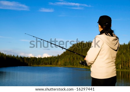 girl fishing in a calm lapland lake on a warm summers day - stock photo