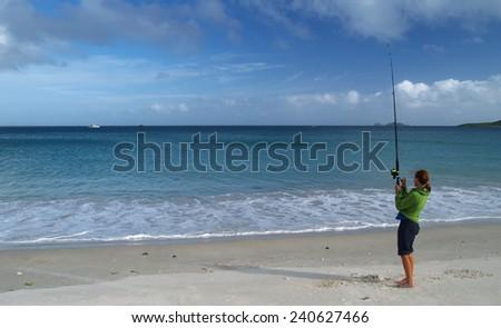Girl fishing on the beach, New Zealand - stock photo