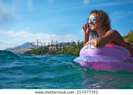girl floating on a mattress in the Adriatic Sea - stock photo