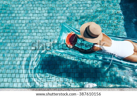 Girl floating on beach mattress and eating watermelon in the blue pool. Tropical fruit diet. Summer holiday idyllic. Top view. - stock photo