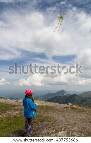 Girl fly the kite on the top of the mountain - stock photo