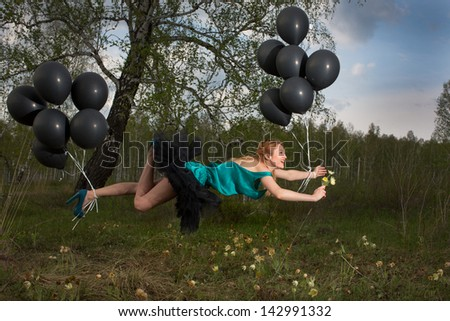 Girl flying above the ground tied with black beads