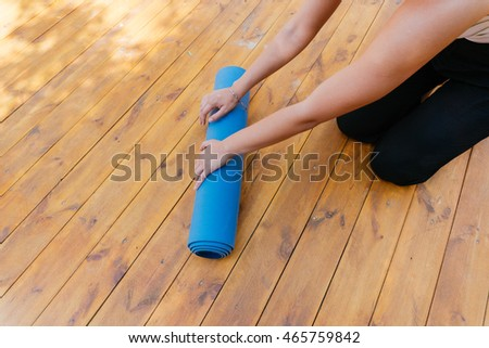 Girl fold your Mat after yoga class, private yoga classes. Yoga on a wooden floor