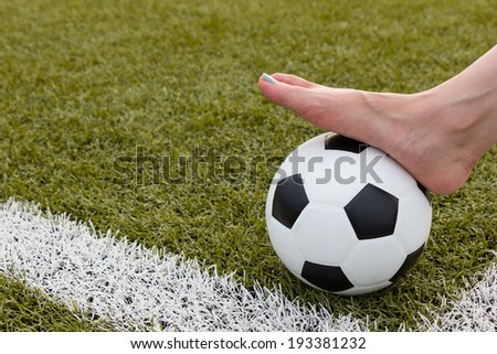 girl foot on the soccer ball on green field morning