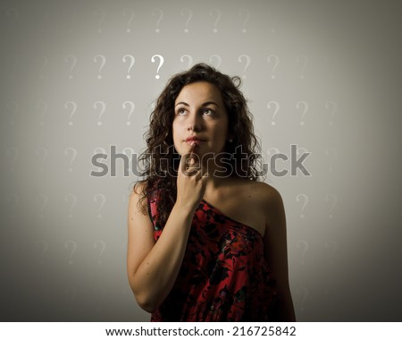 Girl full of doubts and hesitation. Girl and many question marks above head. Young woman doing something.  - stock photo