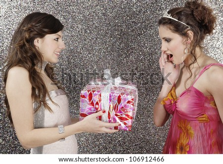Girl giving a wrapped gift to her friend against a silver glitter background.