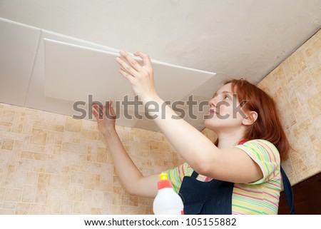 Girl glues ceiling tile at home