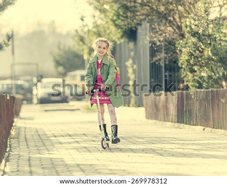 girl goes to school on a scooter - stock photo