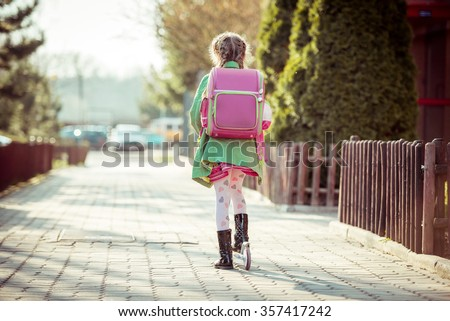 girl goes to school on a scooter. back view - stock photo