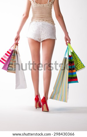 Girl goes with the shopping bags. Beautiful slim legs. Red high-heeled shoes.