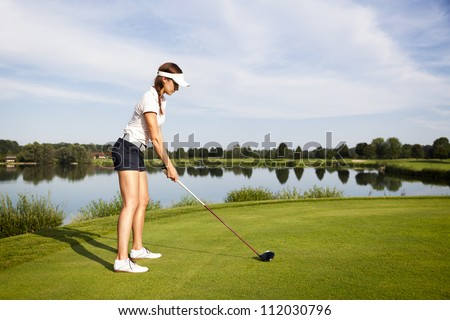 Girl golf player focusing on golf ball to tee off in tee-box. - stock photo