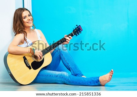 girl guitar play and sings . young model sitting on a floor. teenager style portrait. - stock photo