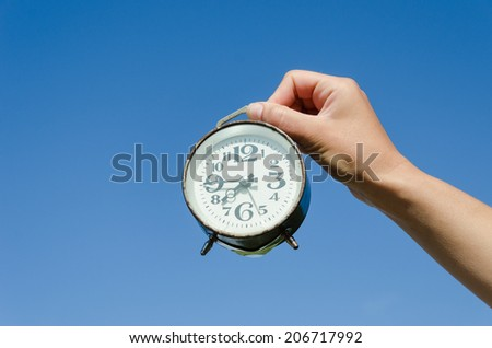 girl hand hold small old retro alarm clock with large black numerals on blue sky background  - stock photo