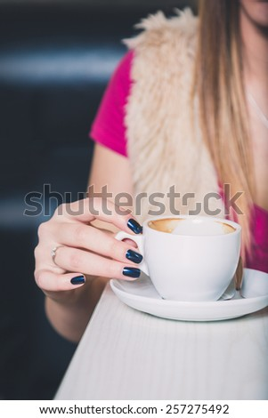 Girl hand holding coffee cup - stock photo