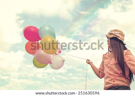 Girl hand holding multicolored balloons done with a retro vintage instagram filter effect, concept of happy birth day in summer and wedding honeymoon party (Vintage color tone paper texture) - stock photo