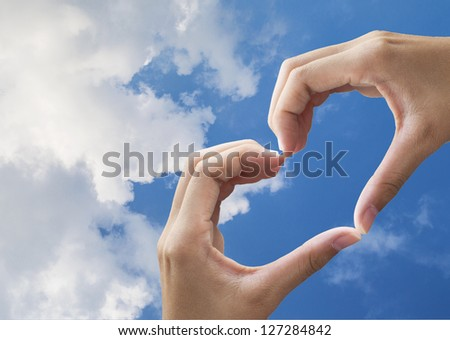 Girl hand in heart form love blue sky - stock photo