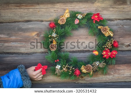 Girl hand is holding red bow and hanging on rustic log cabin wall with X-mas wreath - stock photo