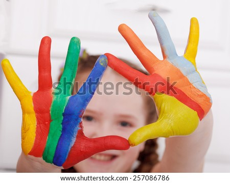 Girl hands painted in bright colors, ready for hand prints