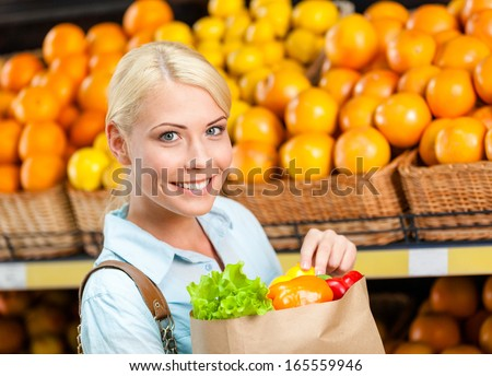 Girl hands paper bag with fresh vegetables against the shelves of fruits in the shopping mall