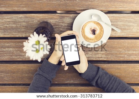 Girl hands with blank smartphone, cup of coffee and flowers on a wooden table - stock photo