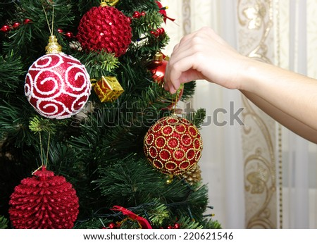 girl hanging decorative toy ball on Christmas tree branch  - stock photo
