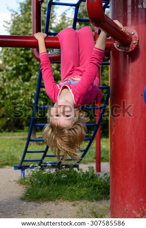 Girl hanging upside down on playground in summer