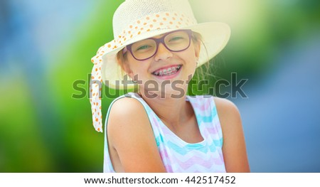 Girl.Happy girl teen pre teen. Girl with glasses. Girl with teeth braces. Young cute caucasian blond girl in summer outfit. - stock photo