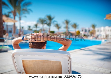 girl has a rest in the summer by the sea on a lounger.