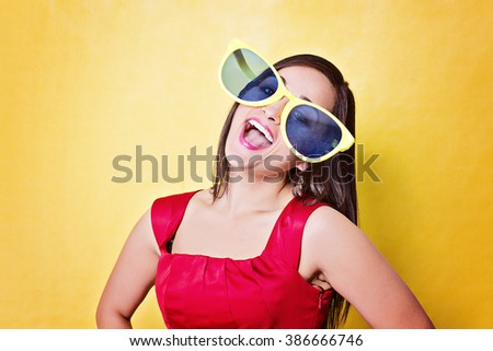 Girl have fun in big blue glasses on yellow background
