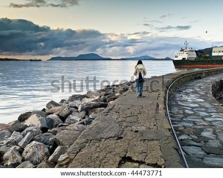 Girl having a walk in the docks of Alesund - stock photo
