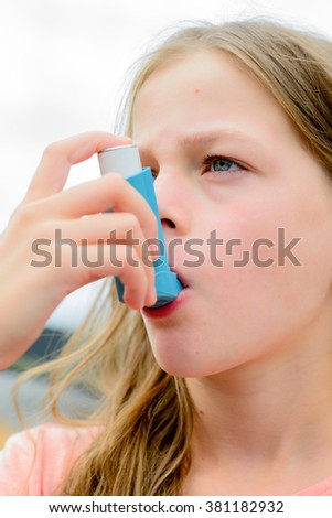 Girl having asthma allergy using the asthma inhaler for being healthy - shallow depth of field