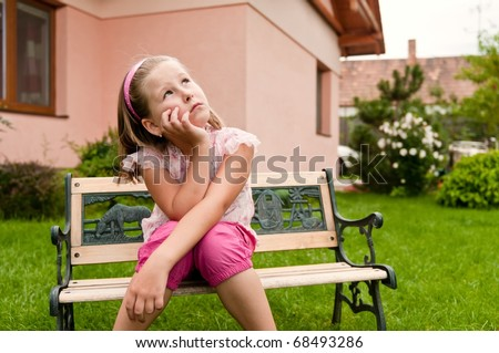 Girl having big problems - sitting on bench in backyard with family house behind