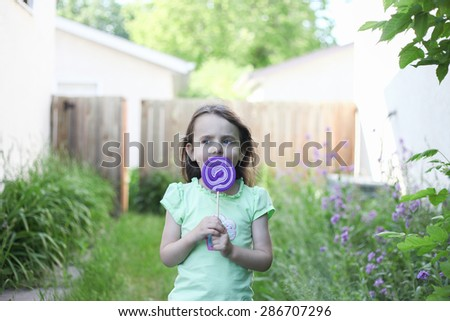Girl having fun licking lollipop - stock photo
