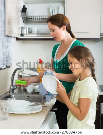 Girl helping mother washing dishes in the kitchen. Focus on girl