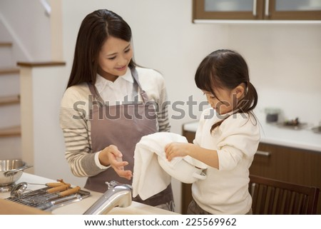 Girl helping with washing dishes - stock photo