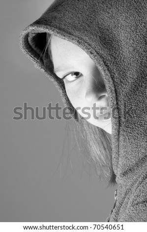 girl hiding behind jacket hood - stock photo