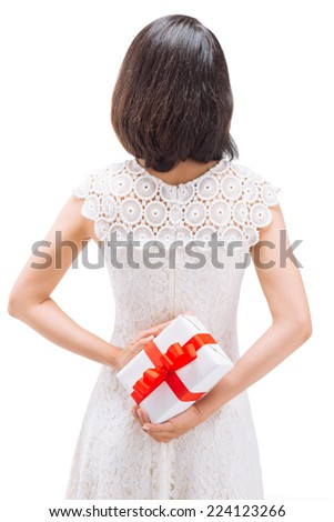 Girl hiding gift behind her back, rear view - stock photo