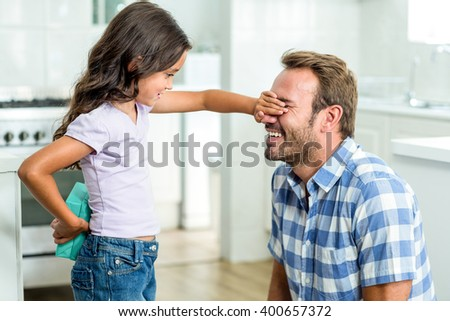 Girl hiding gift while covering happy father eyes in kitchen - stock photo