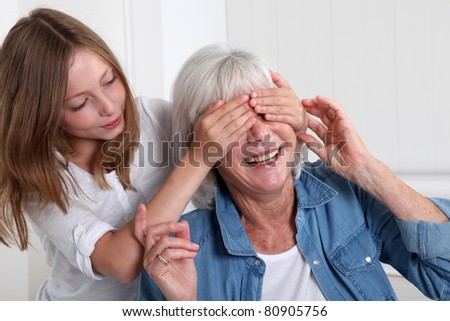 Girl hiding her grandmother's eyes