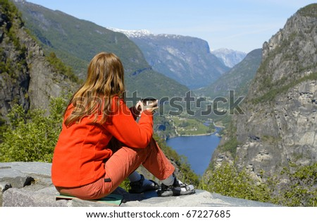 girl hiker on a rest holding a cup of tea and looking at the fjord - stock photo