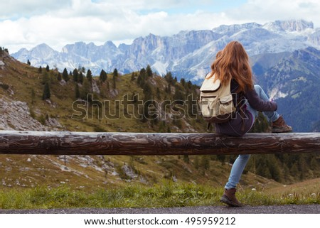 girl hiker sitting  and looking at the snowed mountains. Dolomites, Italy.