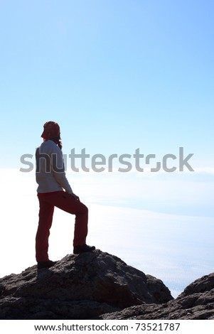girl hiker standing on a rock and looking at the sea - stock photo